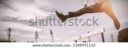 Businessman jumping a hurdle while running on the racing track