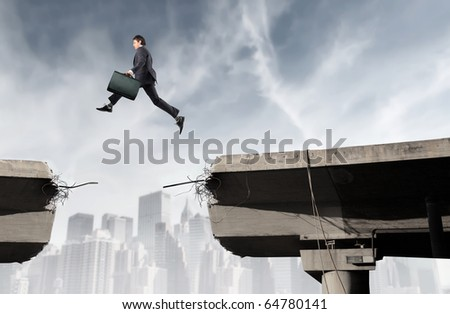 Businessman jumping from a part of a broken bridge to another