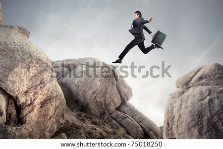 Businessman jumping from a stone to another - stock photo