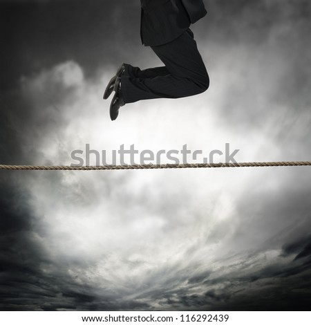 businessman jumping on a rope
