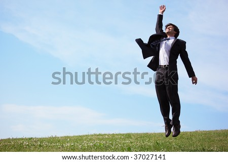 businessman jumping on grass - stock photo
