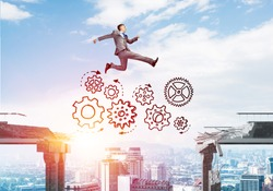 Businessman jumping over gap with gear mechanism in concrete bridge as symbol of overcoming challenges. Cityscape and sunlight on background. 3D rendering.