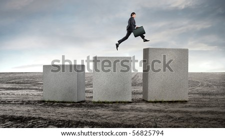 Businessman jumping up to a higher cube