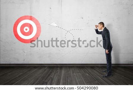 Businessman keeping track of the paper airplane flying right on target. Long-term plan. Distant goal. Total control. Stockfoto ©