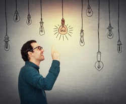 Businessman keeps index finger pointed up, eureka gesture, choosing a hanging glowing light bulb from others switched off. Business worker wears eyeglasses thinking of new ideas, planning concept.