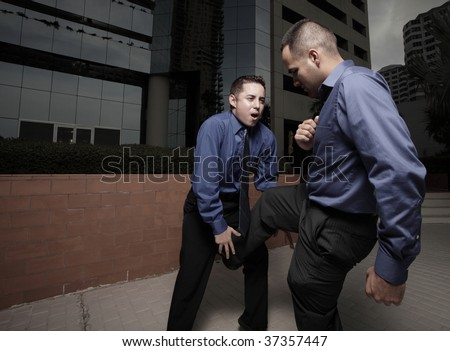 Businessman kicking the other businessman in the groin