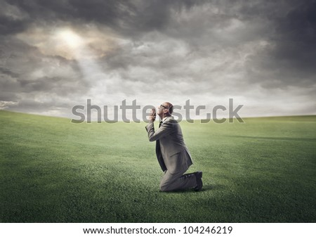 Businessman kneeling on a green meadow and praying