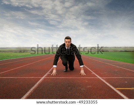 Businessman kneeling on a starting grid