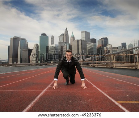 Businessman kneeling on a starting grid with cityscape on the background