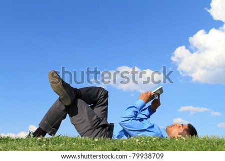 businessman laying down on the grass and working with tablet