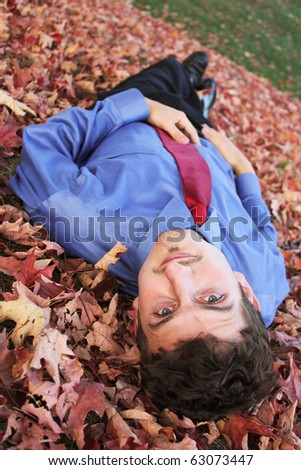 Businessman laying in Fall leaves