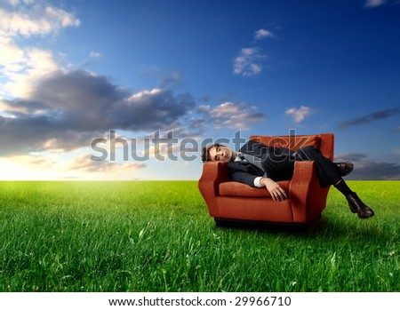 businessman laying on an armchair in a grass field