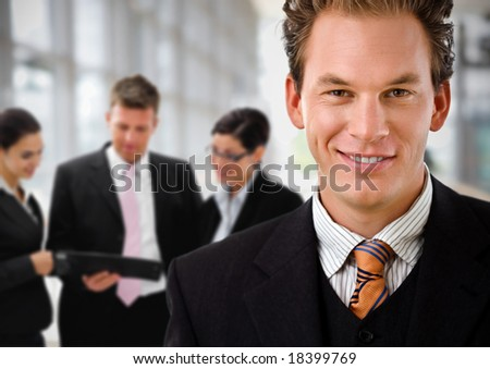 Businessman leading team of business people working in background.