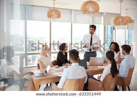 Businessman Leads Meeting Around Table Shot Through Door