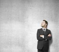 businessman leaning against a concrete wall and thinking