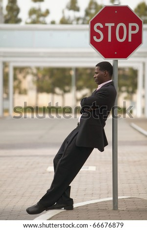 Businessman leaning against stop sign