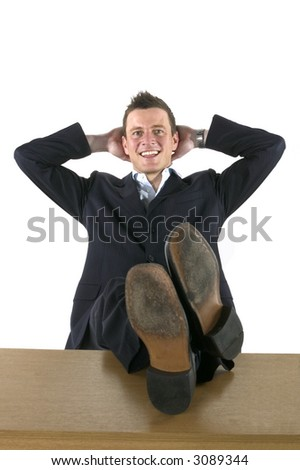 Businessman leaning back on a chair with his feet on the desk