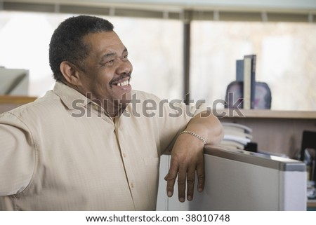 Businessman leaning on a cubicle in an office
