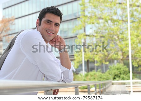 Businessman leaning on a rail in the sunshine - stock photo