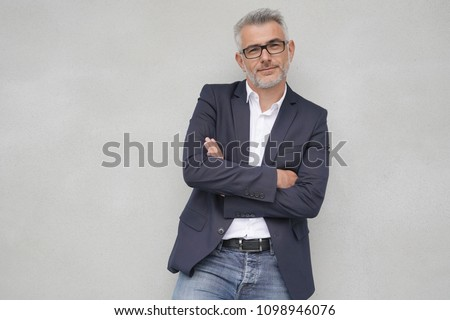 Businessman leaning on concrete wall, isolated