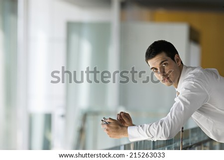 Businessman leaning on glass surface, holding personal electronic organiser, side view, portrait