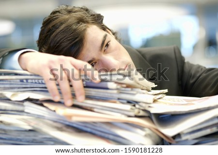 Businessman leaning on pile of paperwork