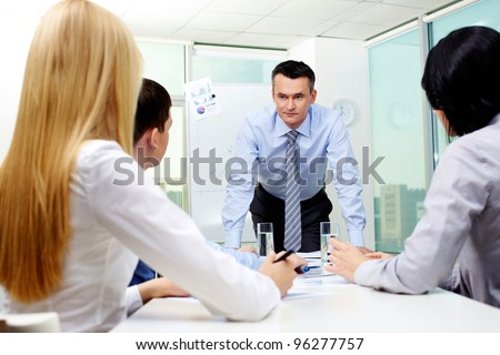 Businessman leaning upon table looking at his colleagues pensively