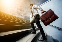 Businessman leap up the stairs to the light.He is boldly and active.. his hand hold a brown leather briefcase.