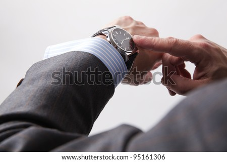 Businessman look his watch, isolated on a grey background Stockfoto ©