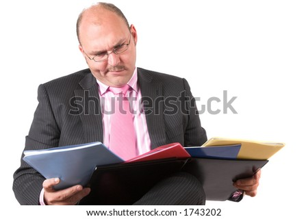 Businessman looking a little puzzled at his coloured folders