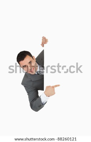 Businessman looking around the corner and is pointing against a white background