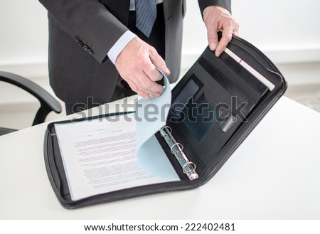 Businessman looking at a document in his briefcase Foto d'archivio ©