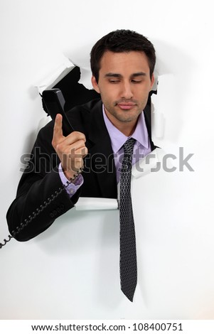 Businessman looking at a telephone handset