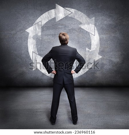 businessman looking at a wall with a loop sign #236960116