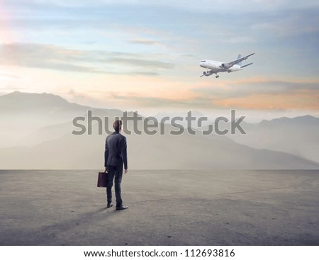 Businessman looking at an airplane in a wasteland
