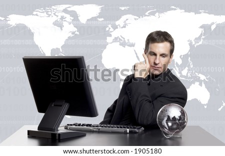 Businessman looking at an earth globe on his desk with an earth map behind him.