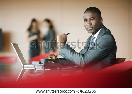 Businessman looking at camera, colleagues on background