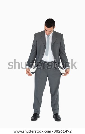 Businessman looking at empty pockets against a white background