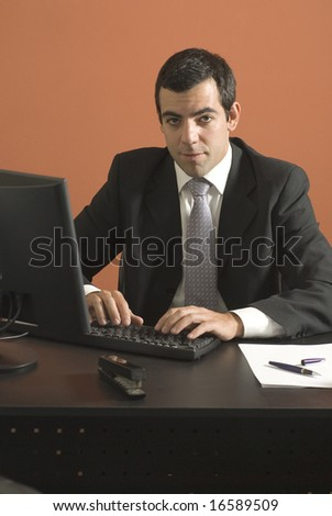 Businessman looking at his laptop computer at his desk. Vertically framed photograph.