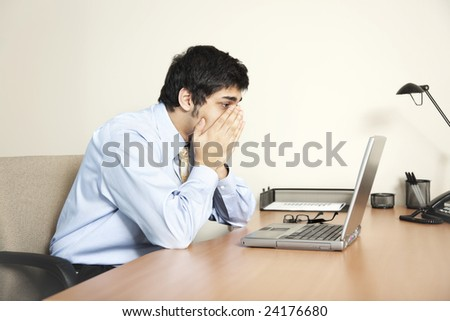 Businessman looking at his laptop computer screen as if faced with a big problem