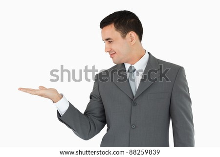 Businessman looking at his palm against a white background