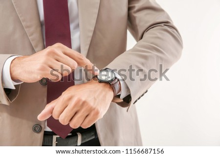 Businessman looking at his watch on light background, closeup. Time management concept #1156687156