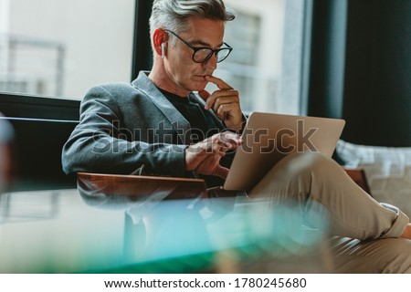 Businessman looking at laptop and thinking. Businessman reading emails on laptop in office lobby.