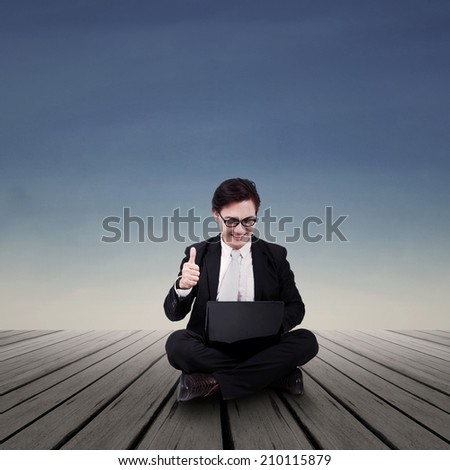 Businessman looking at laptop with ok sign #210115879