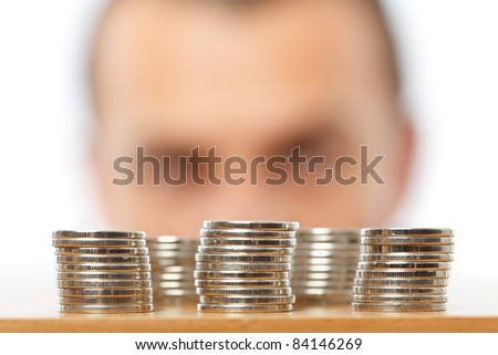 Businessman looking at piles of pennies, financial crisis or savings concept