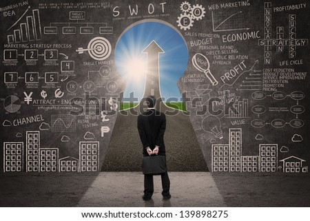 Businessman looking at up arrow sign through a keyhole with written blackboard