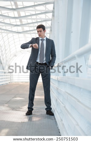 Businessman looking at watches while walking outside modern building