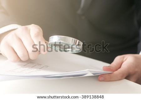 businessman  looking documents through the magnifying glass