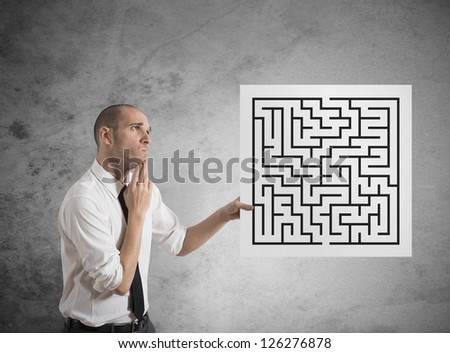 Businessman looking for a solution of a maze