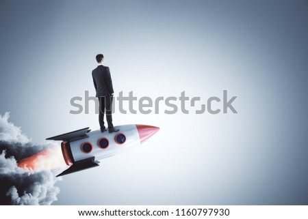 Businessman looking into the distance on abstract launching rocket on gray background. Startup and research concept. #1160797930